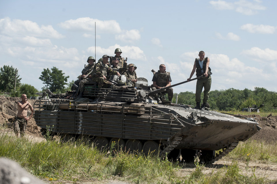 Photo - Ukrainian troops atop an APC at a checkpoint near Slovyansk, eastern Ukraine, Saturday, July 5, 2014. Ukraine's forces claimed a significant success against pro-Russian insurgents on Saturday, chasing them from one of their strongholds in the embattled east of the country. Rebels fleeing from the city of Slovyansk vowed to regroup elsewhere and fight on. (AP Photo/Evgeniy Maloletka)