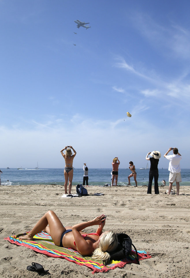 Photo -   Spectators take pictures as the Space Shuttle Endeavour mounted on NASA's Shuttle Carrier Aircraft (SCA) flies near Santa Monica, Calif., Friday, Sept. 21, 2012. (AP Photo/Jae C. Hong)