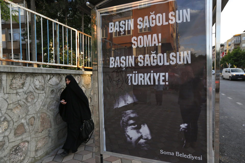 Photo - A woman walks past a bus stop with a poster offering condolences in Turkish to Soma and Turkey, in Soma, western Turkey, where the mine accident occurred, Saturday, May 17, 2014. An explosion and fire at a coal mine in Soma, some 250 kilometers (155 miles) south of Istanbul, killed hundreds of workers in one of the worst mining disasters in Turkish history. (AP Photo/Lefteris Pitarakis)