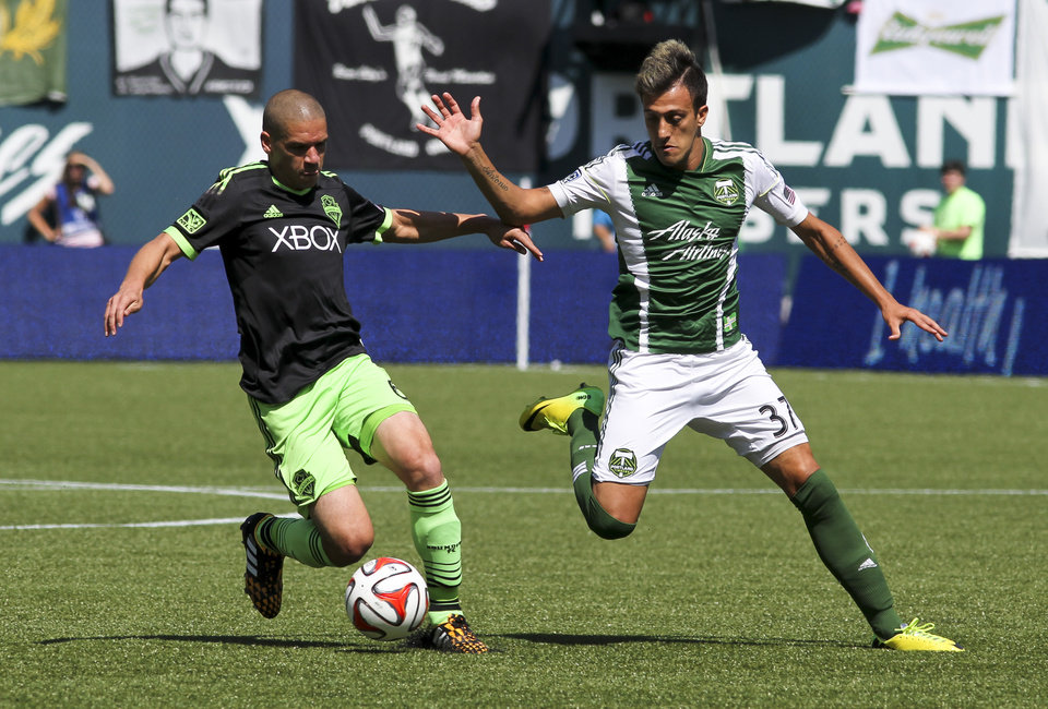 Photo - Portland Timbers' Maximiliano Urruti right, and and Seattle Sounders' Osvaldo Alonso, left, vie for control of the ball during an MLS soccer game in Portland, Ore., Sunday, Aug. 24, 2014. (AP Photo/Natalie Behring)