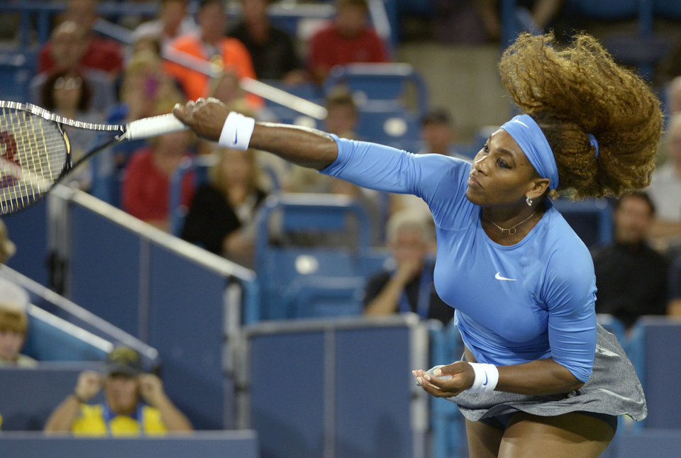 Photo - Serena Williams, from the United States, follows through on a serve to Mona Barthel, from Germany, at the Western & Southern Open tennis tournament, Thursday, Aug. 15, 2013, in Mason, Ohio. (AP Photo/Michael E. Keating)