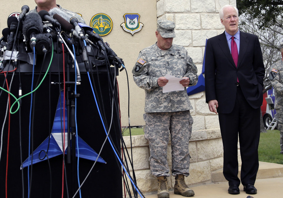 Photo - Lt. Gen. Mark Milley, left, and U.S. Sen. John Cornyn, right, wait to talk to the media near Fort Hood's main gate, Thursday, April 3, 2014, in Fort Hood, Texas. A soldier opened fire Wednesday on fellow service members at the Fort Hood military base, killing three people and wounding 16 before committing suicide. (AP Photo/Eric Gay)