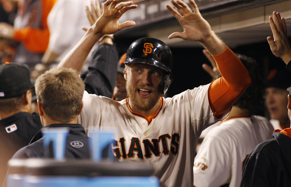Photo - San Francisco Giants' Hunter Pence is greeted in the dugout after scoring against the Miami Marlins during the fifth inning of a baseball game, Thursday, May 15, 2014, in San Francisco. (AP Photo/George Nikitin)