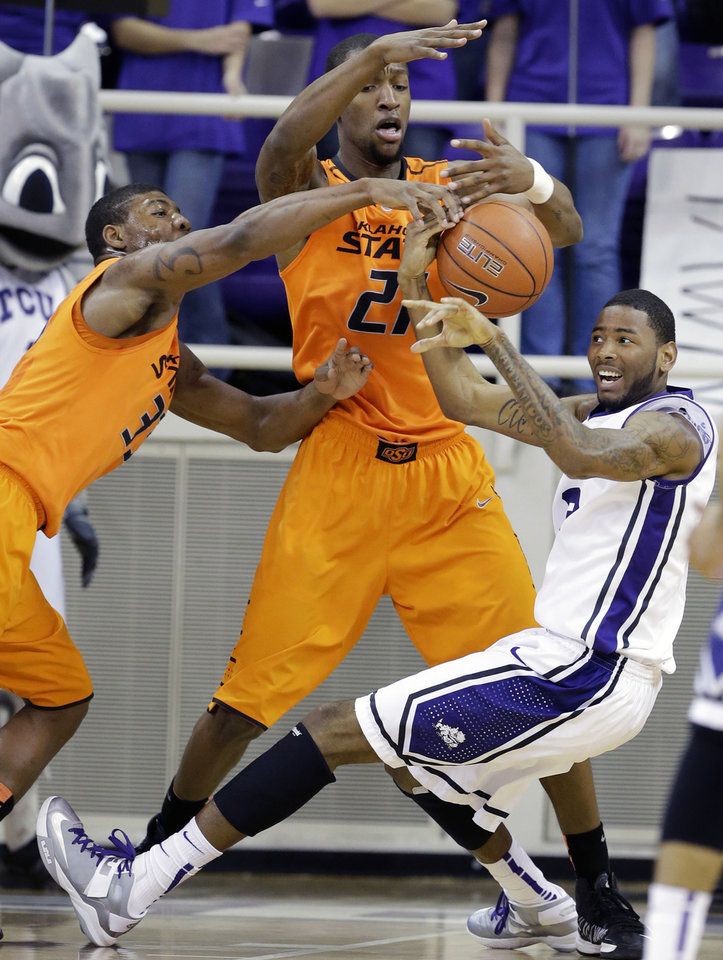 Oklahoma State's Marcus Smart (33) and Kamari Murphy (21) combine to steal the ball away from TCU 's Connell Crossland, right, in the first half of an NCAA college basketball game on Wednesday, Feb. 27, 2013, in Fort Worth, Texas. (AP Photo/Tony Gutierrez) ORG XMIT: TXTG103