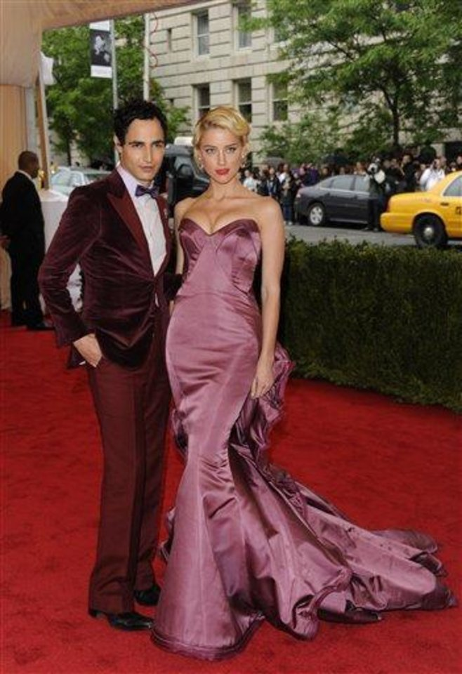 Photo - Designer Zac Posen, left, and actress Amber Heard arrive at the Metropolitan Museum of Art Costume Institute gala benefit, celebrating Elsa Schiaparelli and Miuccia Prada, Monday, May 7, 2012 in New York. (AP Photo/Evan Agostini)