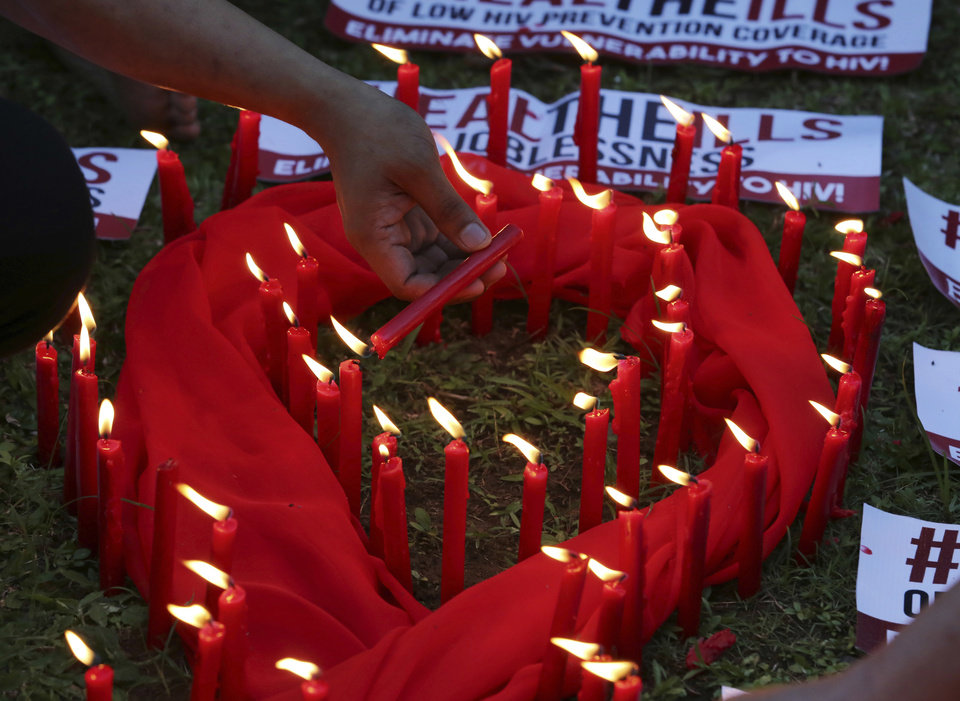 Photo - A Filipino lights candles around an AIDS symbol as he joins an event in observance of World AIDS Day in Quezon city, Philippines on Thursday, Dec. 1, 2016. The group is calling for increased awareness to the rising number of HIV infections and AIDS-related cases and called on the government and other sectors to help break the social stigma brought about by the disease. (AP Photo/Aaron Favila)