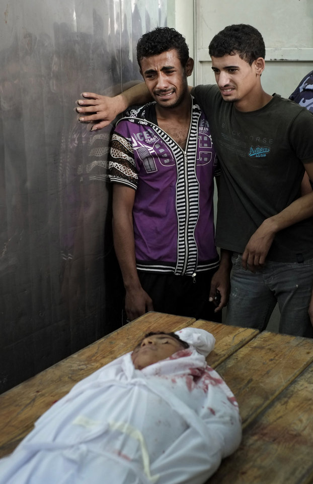 Photo - Palestinian mourners weep as they identify the lifeless body of 9-year-old Rajab Al Shrafi, at the morgue of the Kamal Adwan Hospital in Beit Lahiya, Sunday, Aug. 3, 2014. According to the family, Rajab, his mother Najah, 41, and his cousin Mahmoud, 24, were all killed in the family house earlier on Sunday in an Israeli strike. (AP Photo/Lefteris Pitarakis)