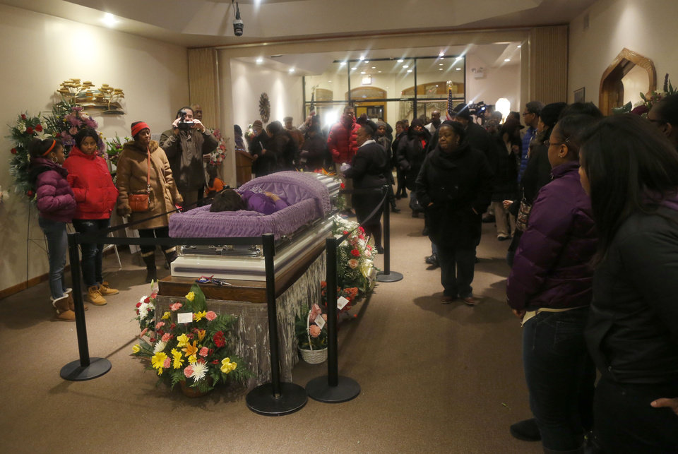 Mourners view the remains of 15-year-old Hadiya Pendleton at the Calahan Funeral Home Friday, Feb. 8, 2013, in Chicago. A White House official says Michelle Obama will attend Saturday's funeral for Pendleton, who was killed after returning home from performing during inauguration festivities for President Barack Obama. Hadiya was killed in a park close to the Obamas' home on Chicago's South Side. Police say a gunman hopped a fence and opened fire on a group of young people, killing the drum majorette. No arrests have been made. (AP Photo/Charles Rex Arbogast, Pool)