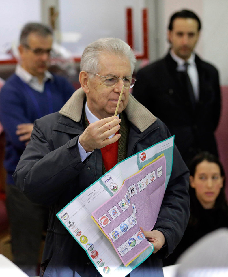 Outgoing Premier Mario Monti holds ballots prior to voting, in Milan, Italy, Sunday, Feb. 24, 2013. Italy votes in a watershed parliamentary election Sunday and Monday that could shape the future of one of Europe's biggest economies. (AP Photo/Luca Bruno)