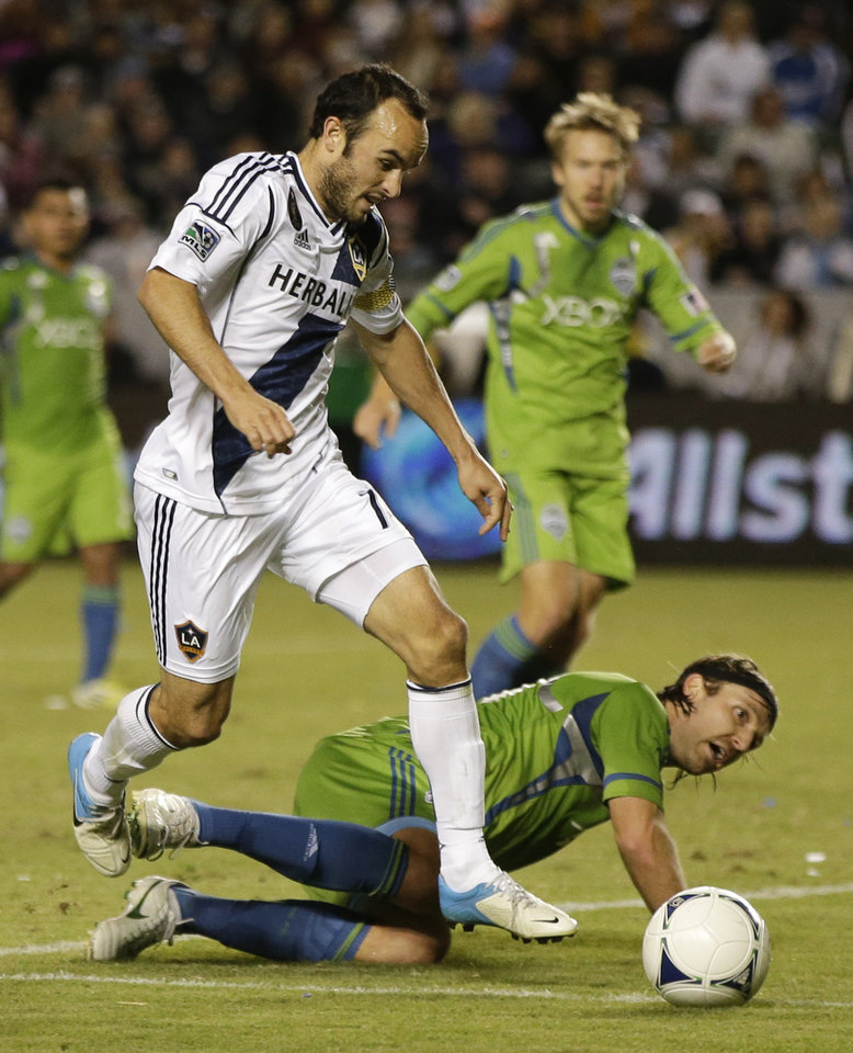 Photo -   Los Angeles Galaxy's Landon Donovan, left, kicks the ball past Seattle Sounders' Steve Zakuani setting up their goal during the first half of an MLS Western Conference finals soccer game in Carson, Calif., Sunday, Nov. 11, 2012. (AP Photo/Chris Carlson)
