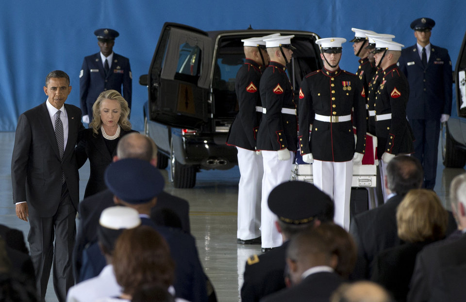 Photo -   President Barack Obama and Secretary of State Hillary Rodham Clinton walk back to their seats after speaking during the Transfer of Remains Ceremony, Friday, Sept. 14, 2012, at Andrews Air Force Base, Md., marking the return to the United States of the remains of the four Americans killed this week in Benghazi, Libya. Behind them at right is one of the flag draped transfer cases of the remains of the four Americans killed this week in Benghazi, Libya. (AP Photo/Carolyn Kaster)