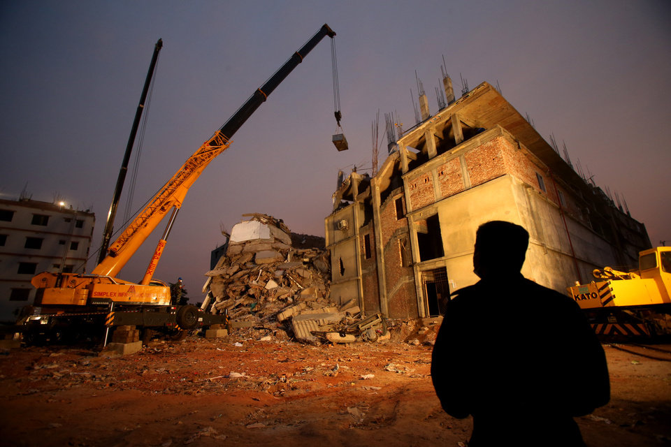 Photo - Firefighters and army personnel continue to work as dusk falls as they dislodge the debris and fallen ceiling of the garment factory building which collapsed in Savar, near Dhaka, Bangladesh, Monday, April 29, 2013. Rescue workers in Bangladesh gave up hopes of finding any more survivors in the remains of a building that collapsed five days ago, and began using heavy machinery on Monday to dislodge the rubble and look for bodies. At least 381 people were killed when the illegally constructed, 8-story Rana Plaza collapsed in a heap on Wednesday morning along with thousands of workers in the five garment factories in the building. (AP Photo/Wong Maye-E)