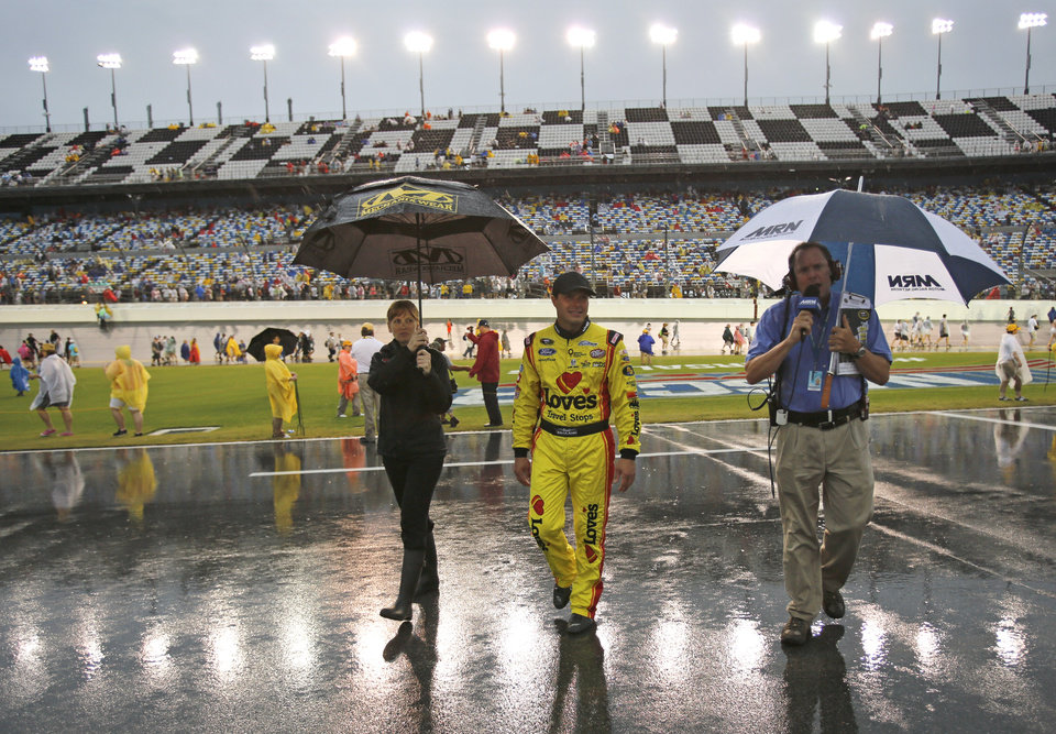 Photo - Driver David Gilliland, center, walks back to the garages after driver introductions the NASCAR Sprint cup Series auto race at Daytona International Speedway in Daytona Beach, Fla., Saturday, July 5, 2014. (AP Photo/Terry Renna)