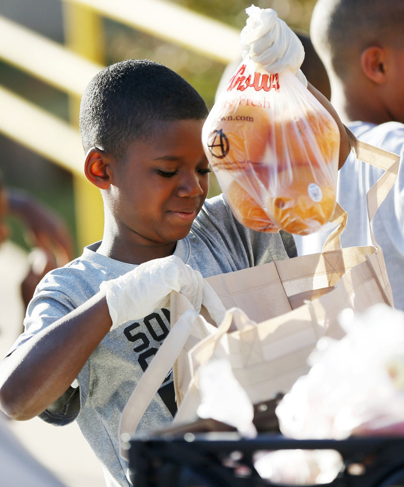 Photo - Paul Wright, 8, loads oranges into a sack of fruits and vegetables he received during a the Free Farmers Market as part of Food Day activities at the Salvation Army Boys and Girls Club, 2808 SE 44th St., one of the Regional Food Bank of Oklahoma's Kids Cafe locations, in Oklahoma City, Thursday, Oct. 24, 2013. Photo by Nate Billings, The Oklahoman