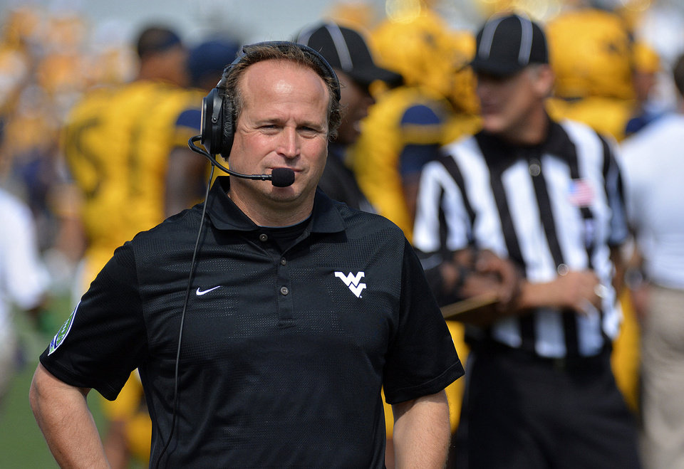 West Virginia coach Dana Holgorsen watches from the sideline during the first quarter of an NCAA college football game against Oklahoma State in Morgantown, W.Va., on Saturday, Sept. 28, 2013. (AP Photo/Tyler Evert) ORG XMIT: WVTE101