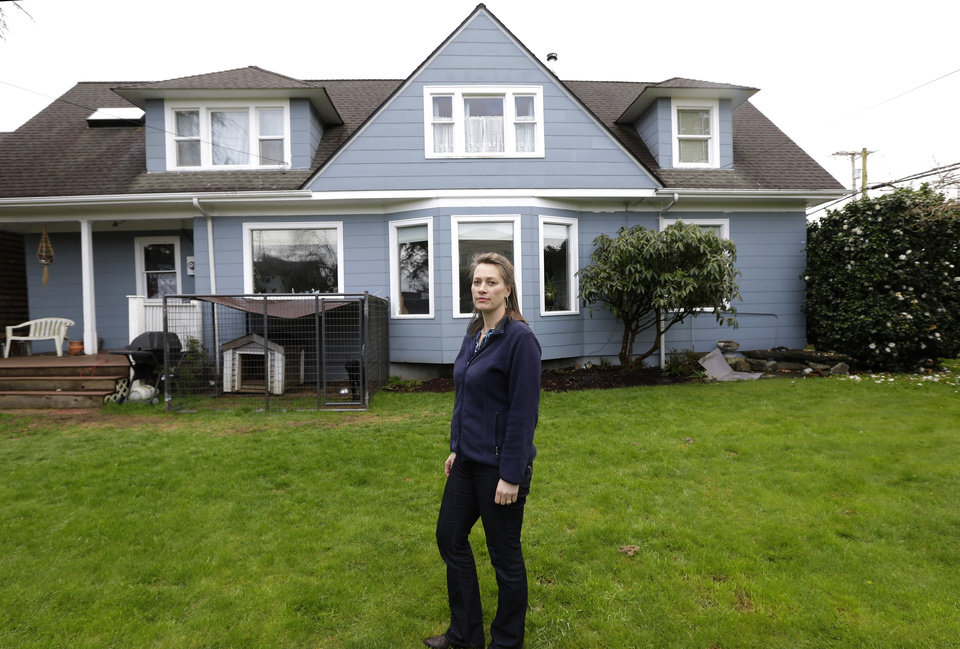 Photo - Erica Hollen stands in the yard of her home in Hoquiam, Wash. on Monday, March 18, 2014. Hollen is worried that possible food insurance rate increases would be unaffordable or prevent her and her husband from eventually selling their home. (AP Photo/Ted S. Warren)