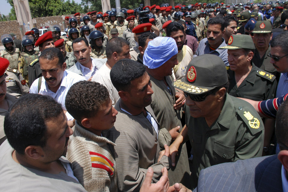 Photo -   Field Marshal Hussein Tantawi, right, the head of Egypt's ruling Supreme Council of the Armed Forces (SCAF), greets mourners at a military funeral for Cpl. Samir Anwar Ismail, a commando killed in clashes with protesters in Cairo, Egypt, Saturday, May 5, 2012. Lawyers say authorities have detained over 300 Egyptian protesters including 18 women following clashes outside the country's Defense Ministry, accused of attacking troops and disrupting public order.(AP Photo)
