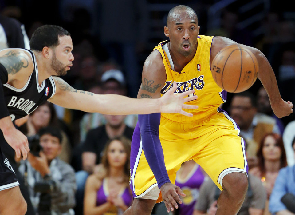Los Angeles Lakers' Kobe Bryant, right, and Brooklyn Nets' Deron Williams go after a loose ball in the first half of an NBA basketball game in Los Angeles, Tuesday, Nov. 20, 2012. (AP Photo/Jae C. Hong)