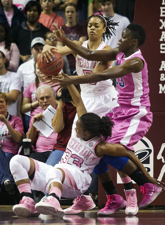 Photo - Texas A&M guard Courtney Walker (33) and forward Kristi Bellock (5) battle for the ball against Kentucky center Samarie Walker (23) during the first half of an NCAA college basketball game, Monday, Feb. 18, 2013, in College Station, Texas. (AP Photo/Patric Schneider)