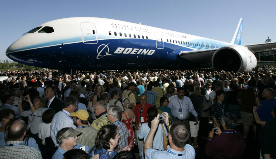 Photo - FILE - In this July 8, 2007, file photo, visitors  look at and take photos of the first production model of the new Boeing 787 airplane after it was unveiled to an audience of several thousand at Boeing's assembly plant in Everett, Wash. The Boeing 787 was a plane that promised to be lighter and more technologically advanced than any other, but once production started, the gap between vision and reality quickly widened. The jet that was eventually dubbed the Dreamliner became plagued with manufacturing delays, cost overruns and sinking worker morale. (AP Photo/Ted S. Warren, File)