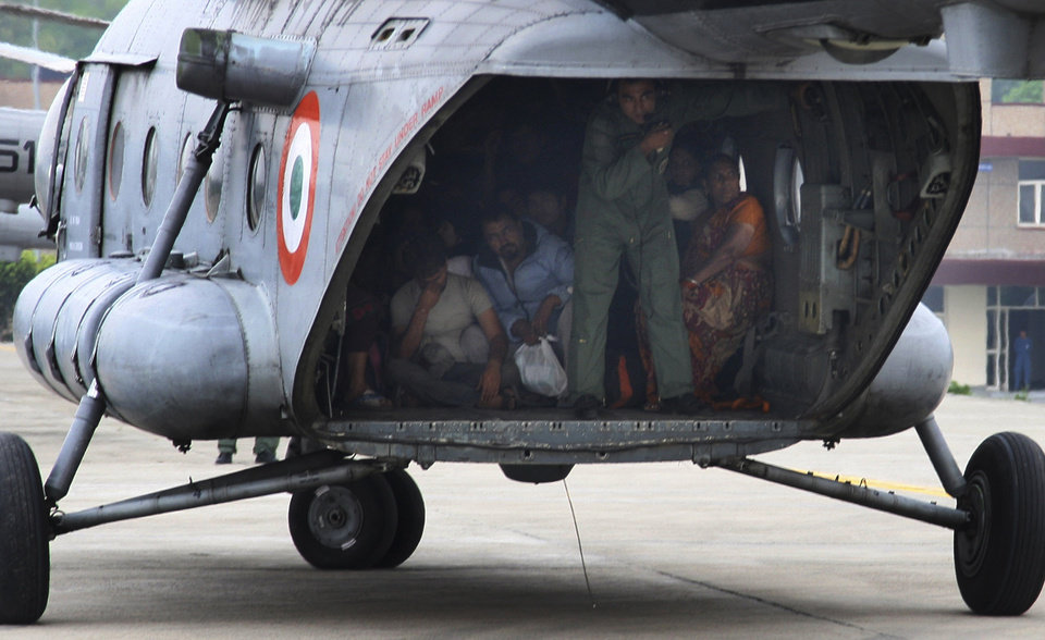 Photo - In this Thursday, June 20, 2013 photo, Indian Air Force personnel carry stranded pilgrims rescued from northern Indian state of Uttarakhand, India. Uttrakhand spokesman Amit Chandola said the rescue operation centered on evacuating nearly 27,000 people trapped in the worst-hit Kedarnath temple area - one of the holiest Hindu temples dedicated to Lord Shiva, located atop the Garhwal Himalayan range. (AP Photo)