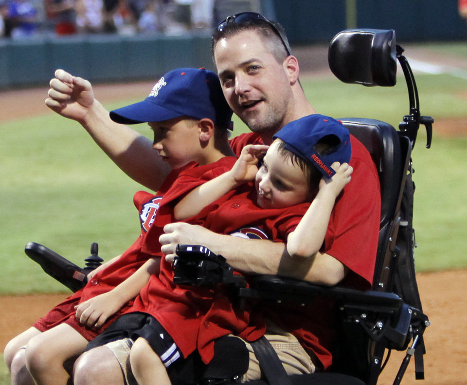 Photo - Oklahoma City police officer Chad Peery ackowledges fans with son McKade, 6, left, and Morgan, 4, on his lap as he is applauded after the third inning as part of the