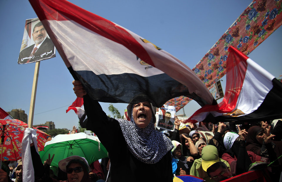 Photo - Supporters of Egypt's ousted President Mohammed Morsi hold pictures of him and chant slogans during a protest at Nasr City, where protesters have installed their camp and hold their daily rally, in Cairo, Egypt, Friday, July 26, 2013. Political allies of Egypt's military lined up behind its call for huge rallies Friday to show support for the country's top general, Abdel-Fattah el-Sissi, pushing toward a collision with Islamist opponents who are also calling for rallies demanding the return of Mohammed Morsi, the nation's ousted president. (AP Photo/Khalil Hamra)