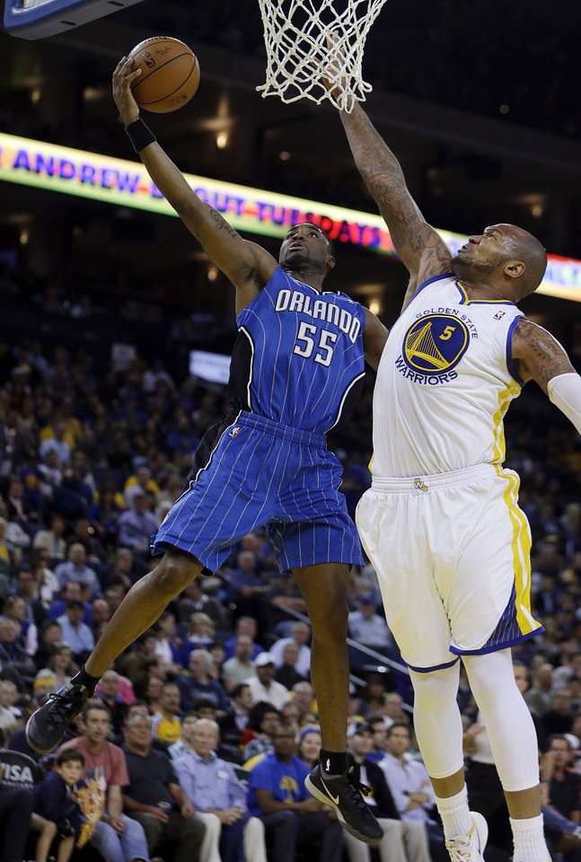 Photo - Orlando Magic guard E'Twaun Moore, left, lays up a shot against Golden State Warriors' Marreese Speights (5) during the first half of an NBA basketball game Tuesday, March 18, 2014, in Oakland, Calif. (AP Photo/Ben Margot)