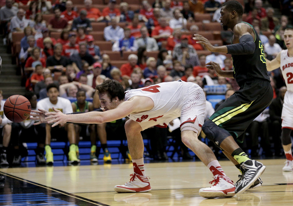 Photo - Wisconsin forward Frank Kaminsky, left, reaches for the ball as Baylor forward Cory Jefferson defends during the second half of an NCAA men's college basketball tournament regional semifinal, Thursday, March 27, 2014, in Anaheim, Calif. (AP Photo/Jae C. Hong)