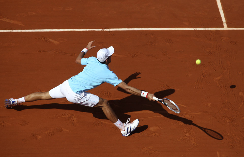 Photo - Serbia's Novak Djokovic returns the ball to Spain's Rafael Nadal during their final match of  the French Open tennis tournament at the Roland Garros stadium, in Paris, France, Sunday, June 8, 2014. (AP Photo/David Vincent)