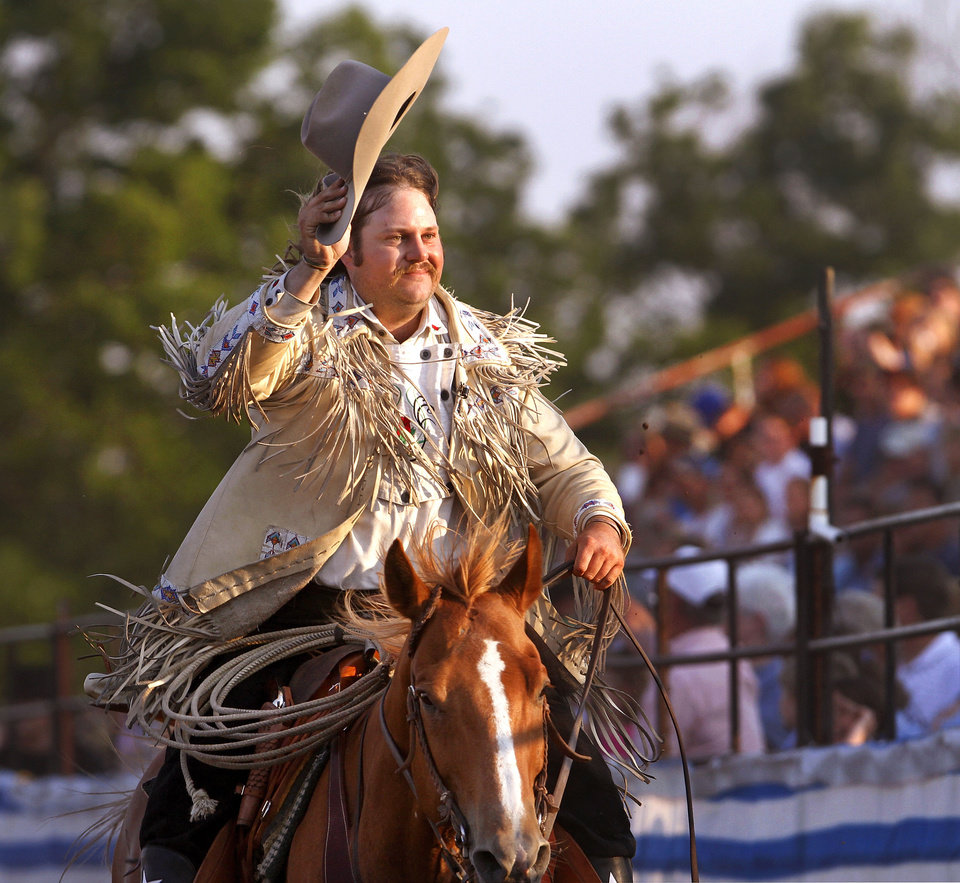 Photo - Kevin Webb, who plays Pawnee Bill, tips his hat June 23 to the cheering crowd as he rides in front of the stands during the Pawnee Bill Wild West Show in Pawnee.