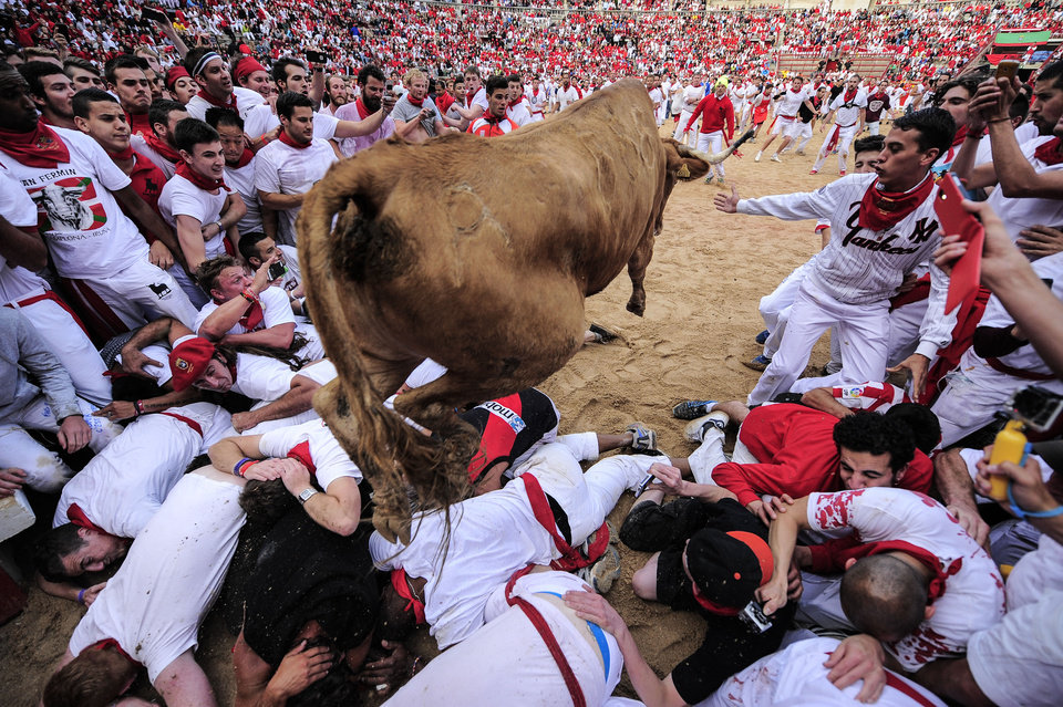 Photo - A cow jumps over revelers which wait the animal on the bull ring, at the San Fermin festival, in Pamplona, Spain, Tuesday, July 8, 2014. Revelers from around the world in Pamplona take part in the eight-day of the running of the bulls glorified by Ernest Hemingway's 1926 novel
