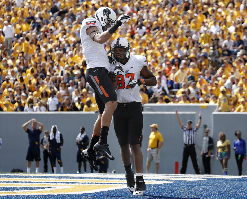 Photo - Oklahoma State's Marcell Ateman (3) and Oklahoma State's Tracy Moore (87) celebrate a touchdown during a college football game between the Oklahoma State University and West Virginia University on Mountaineer Field at Milan Puskar Stadium in Morgantown, W. Va.,   Saturday, Sept. 28, 2013. Photo by Sarah Phipps, The Oklahoman