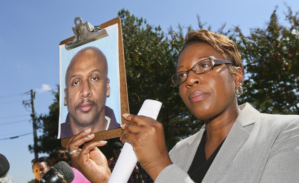 Photo -   Fulton County Police public information officer Kay Lester holds up the picture of Floyd Palmer, the suspect being sought in a fatal shooting at World Changers Church International in College Park, Ga. Wednesday, Oct. 24, 2012. A church volunteer leading prayer was shot and killed inside the chapel of the megachurch. (AP Photo/Atlanta Journal-Constitution, John Spink) MARIETTA DAILY OUT; GWINNETT DAILY POST OUT; LOCAL TV OUT; WXIA-TV OUT; WGCL-TV OUT