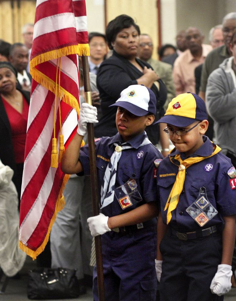 Photo - Brice Knight carries the American flag as he and fellow Cub Scout Daiden Jones participate in the posting of the colors at the start of the 16th annual Midwest City Dr. Martin Luther King, Jr. Prayer Breakfast inside the Reed Conference Center Monday morning, Jan. 21, 2013. The scouts are members of Pack 1864 from St.  John Missionary Baptist Church. The theme of this year's event is