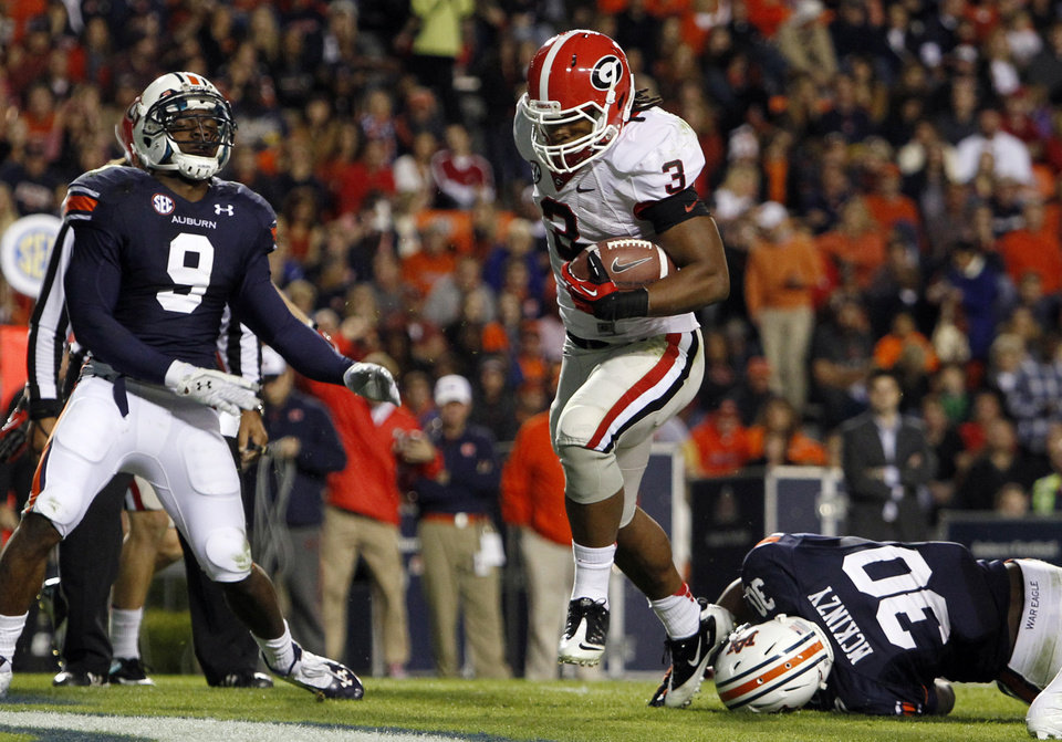 Photo -   Georgia running back Todd Gurley (3) carries the ball over Auburn linebacker Cassanova McKinzy (30) for a touchdown during the first half of an NCAA college football game on Saturday, Nov. 10, 2012, in Auburn, Ala. (AP Photo/Butch Dill)