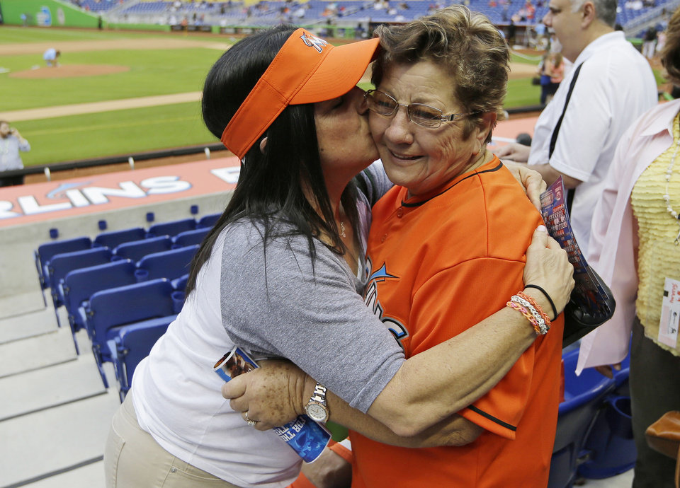 Photo - Olga Fernandez, of Cuba, right, gets a kiss from Ana Olga Cairo, left, before an opening day baseball game between the Miami Marlins and Colorado Rockies, Monday, March 31, 2014, in Miami. Olga Fernandez is the grandmother, of starting Marlins pitcher Jose Fernandez, and came from Cuba to see him pitch. (AP Photo/Lynne Sladky)