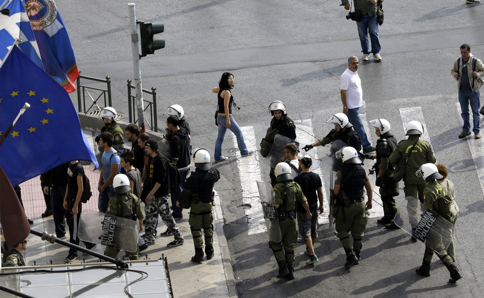 Photo -   Civilians are detained as precaution by riot police prior to an protest in Athens on Tuesday Oct. 9, 2012. German Chancellor Angela Merkel makes her first visit to Greece since the eurozone crisis began here three years ago. Her five-hour stop is seen by the government as a historic boost for the country's future in Europe's shared currency, but by protesters as a harbinger of more austerity and hardship. More than 7,000 police will be on hand, cordoning off parks and other sections of central Athens, to keep demonstrators away from the German leader who is due to arrive Tuesday in the Greek capital for talks with conservative Prime Minister Antonis Samaras. (AP Photo/Dimitri Messinis)