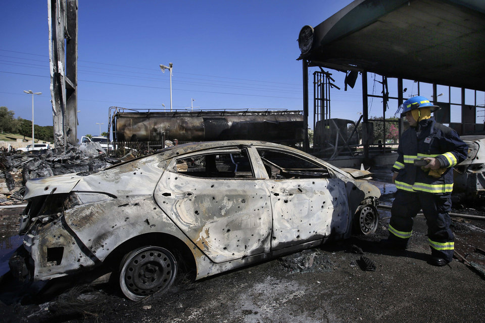 Photo - A firefighter stands at a gas station that was hit by a rocket fired from the Gaza Strip in the city of Ashdod, Israel, Friday, July 11, 2014. The attack on the gas station in Ashdod looked to be the most serious attack in Israel in the four days of fighting that has seen Israel deliver a heavy blow to Gaza's Hamas leaders. The military have carried out more than 1,000 strikes against Gaza targets that have killed at least 95 people, including dozens of civilians.(AP Photo/Tsafrir Abayov)