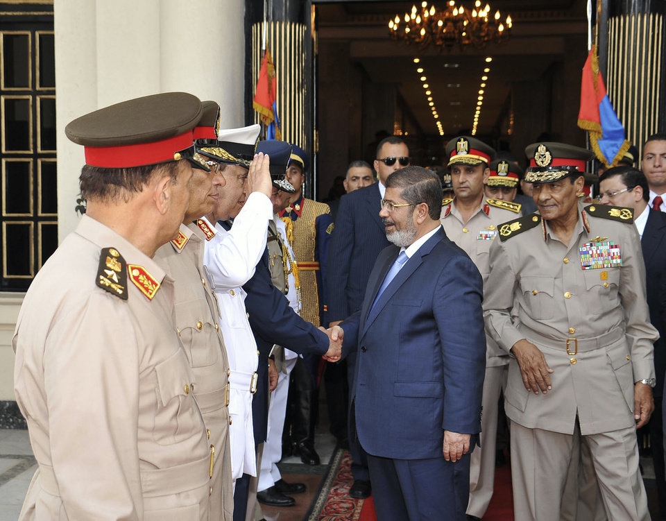 In this photo released by the office of the Egyptian Presidency, President Mohammed Morsi, center, shakes hands with military officers in Cairo, Egypt, Tuesday, July 17, 2012. Field Marshal Hussein Tantawi is seen at right. Egypt�s President Mohammed Morsi hailed the Egyptian army and its commanders at a time the newly elected Islamist president and the military council, which took power after ouster of Hosni Mubarak last year, are in mid of power struggle. (AP Photo/Sheriff Abd El Minoem, Egyptian Presidency)