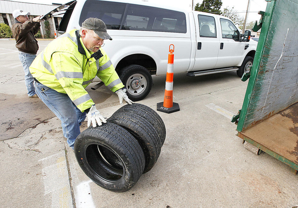 Photo - City worker Jeff Whitfield removes old tires from a truck during  Edmond's annual Operation Clean Streets.  PHOTOS BY  PAUL HELLSTERN,  THE OKLAHOMAN