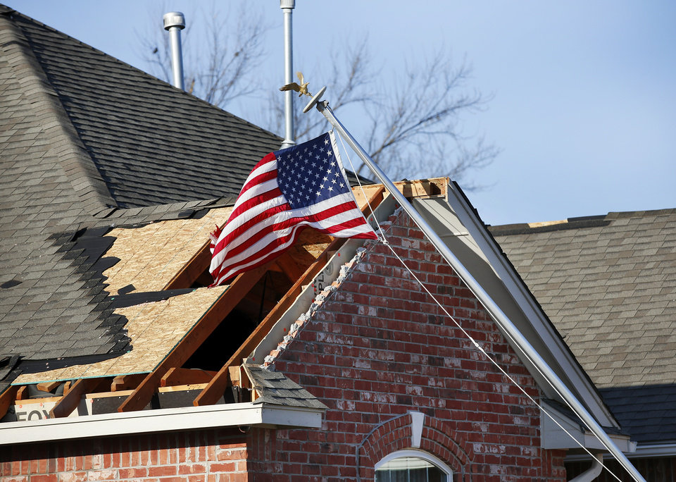 Photo - NW 2nd Street.  The flag still flies despite the flagpole being pulled out of the ground during the tornado. A toppled flagpole in a neighborhood  between NW 5 and Main Street, and between Telephone Rd. and Santa Fe in Moore.  Thursday morning, March 26, 2015, the day after a tornado damaged homes and a school Wednesday evening. Photo by Jim Beckel, The Oklahoman