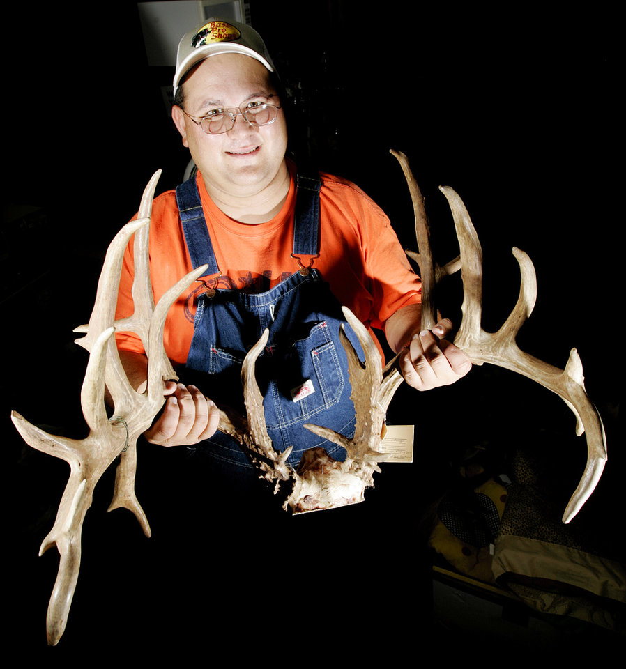 Photo -  DEER ANTLERS: Michael Crossland poses for a photo with his estimated 31-point buck rack at Hillman's Taxidermy, 343 N 5th St., in Yukon, Okla., Aug 2, 2005. By Nate Billings/The Oklahoman