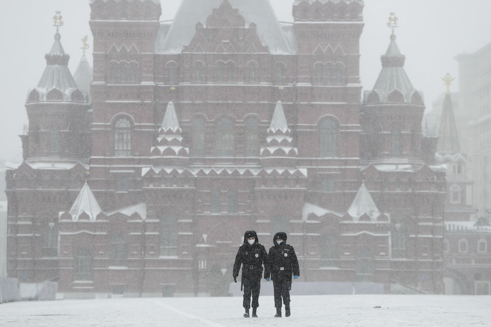 Photo -  Police officers walk across an empty Red Square in Moscow, Russia, Tuesday, March 31, 2020. The Russian capital has woken up to a lockdown obliging most people in the city of 13 million to stay home. The government ordered other regions of the vast country to quickly prepare for the same as Moscow, to stem the spread of the new coronavirus. The new coronavirus causes mild or moderate symptoms for most people, but for some, especially older adults and people with existing health problems, it can cause more severe illness or death. (AP Photo/Pavel Golovkin)