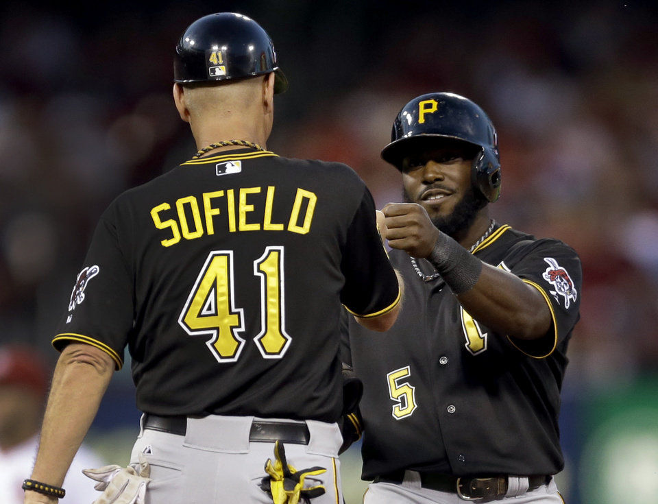 Photo - Pittsburgh Pirates' Josh Harrison, right, is congratulated by first base coach Rick Sofield after hitting a ground-rule double to score two runs during the sixth inning of a baseball game against the St. Louis Cardinals Thursday, July 10, 2014, in St. Louis. (AP Photo/Jeff Roberson)