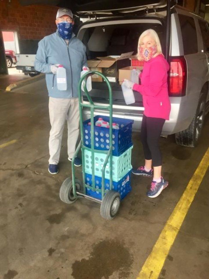 Photo -  Ann Ackerman, president of the Rotary Club of Oklahoma City, and her husband, Wayne Stone, assist in the distribution of hand sanitizer to groups in the Oklahoma City metro area. [PROVIDED]