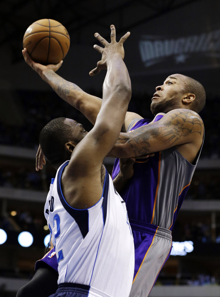 Dallas Mavericks' Elton Brand (42) defends beneath the basket as Phoenix Suns' P.J. Tucker shoots in the first half of an NBA basketball game, Sunday, Jan. 27, 2013, in Dallas. (AP Photo/Tony Gutierrez)