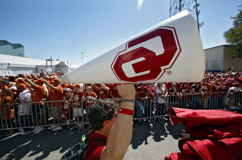 A member of the Oklahoma cheer squad raises the OU bull horn high as he passes Longhorn and Sooner fans as the team arrives for the Red River Rivalry college football game between the University of Oklahoma Sooners (OU) and the University of Texas Longhorns (UT) at the Cotton Bowl on Saturday, Oct. 2, 2010, in Dallas, Texas.   Photo by Chris Landsberger, The Oklahoman