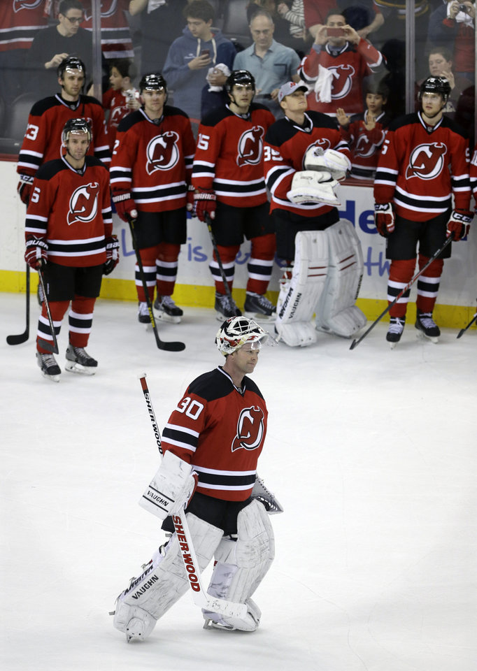 Photo - New Jersey Devils teammates watch as goalie Martin Brodeur skates for the crowd after an NHL hockey game against the Boston Bruins in Newark, N.J., Sunday, April 13, 2014. The Devils won 3-2. (AP Photo/Mel Evans)