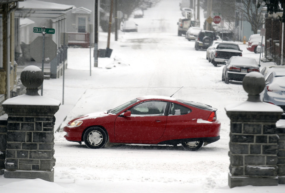 Photo - A car travels in the snow on Tuesday, Jan. 21, 2014, in Annville Township, Pa. The National Weather Service predicts the storm could drop 8 to 12 inches of snow followed by bitterly cold temperatures. (AP Photo/Lebanon Daily News, Jeremy Long)  THE PATRIOT-NEWS OUT